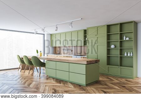 Corner Of Modern Kitchen With White And Green Walls, Wooden Floor, Green Cupboards And Dining Table.