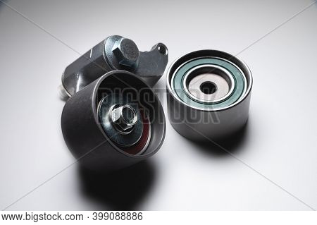 Two Tensioning Rollers Of The Engine Timing Belt On A Gray Background. New Spare Parts For Car Engin