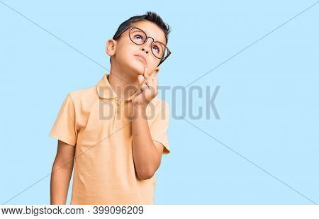 Little cute boy kid wearing casual clothes and glasses serious face thinking about question with hand on chin, thoughtful about confusing idea