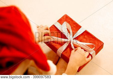 Beautiful Happy Little Caucasian Girl Laughs. Child With A Gift In A New Year's Hat, Unpacking A Gif
