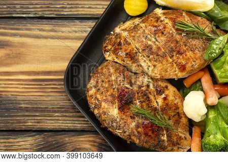 Grilled Chicken Breast In A Skillet With Vegetables And Herbs, Sliced Lemon On A Wooden Board