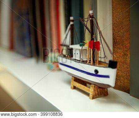 Small Wooden Ship On A Bookshelf, Travel - Nostalgia Concept.
