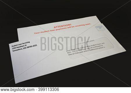 Student Loan Payments Resuming Notice In Envelope On Black Desk, Left Angled.