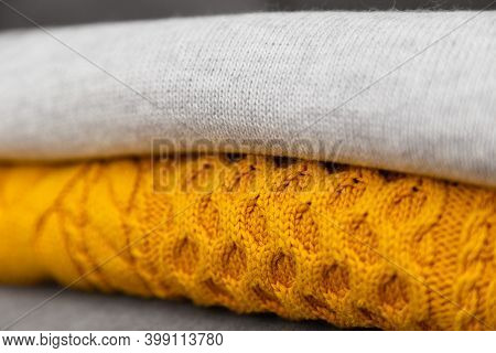 Knitted Pullovers Close Up In Trendy Grey And Yellow Colors. Colors Of The 2021 Year. Stack Of Cozy