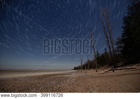 Star Trails On A Full Moon Night With The Beach And Trees In The Foreground, Southampton, Ontario