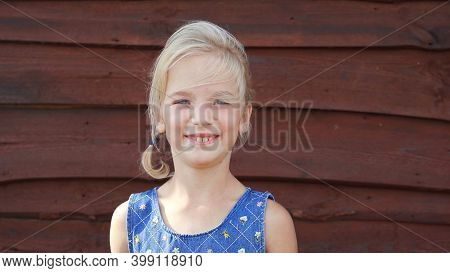Portrait Of A Seven-year-old Girl Against The Background Of A Barn Wall In The Village.