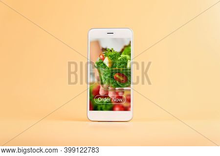 Smartphone On The Orange Background And Show Application Screen For Ordering Salad Online.