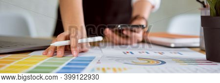 Businesswoman Standing And Holding Digital Pen, Smartphone With Working On Laptop In The Office.