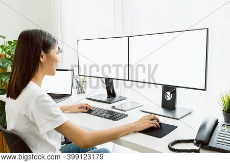 Young Asian Woman Sitting On Chair And Working At The Computer With Blank Screen In Home On The Day