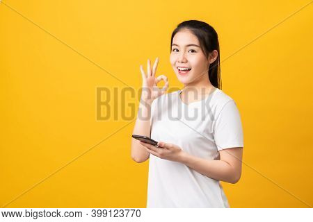 Cheerful Beautiful Asian Woman Holding Smartphone And Shows Ok Sign On Light Yellow Background.