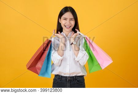 Young Smiling Asian Woman Casual Clothes Holding Multi Coloured Shopping Bags On Light Yellow Backgr