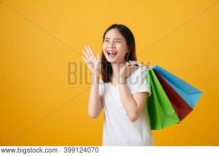 Young Smiling Asian Woman Holding Multi Coloured Shopping Bags And Announcing With Hands To The Mout