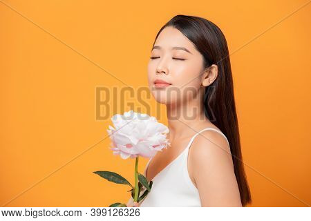 Young Woman Sniffing Pink Peony Flower Closed Her Eyes On Yellow Background