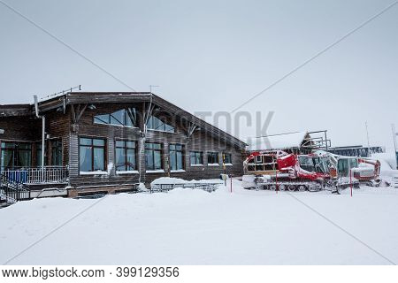 Guest House In A Snowy Ski Resort And A Nearby Snowcat And Other Specialized Tracked Vehicles In Win