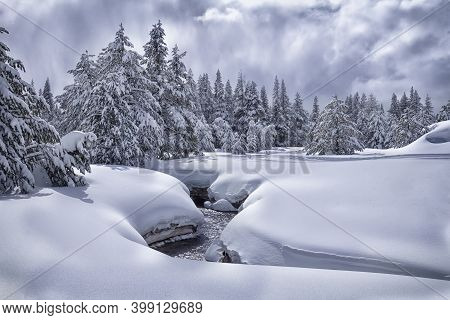 Landscape With Creek In Winter Snowy Forest