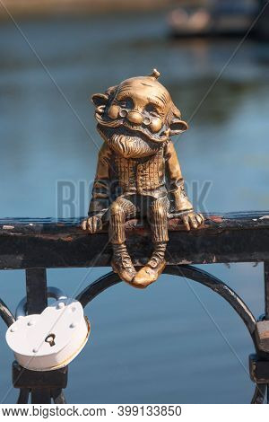 On The Honey Bridge In Kaliningrad (russia), A Bronze Figurine Of A Fairy-tale Gnome Grandfather Is