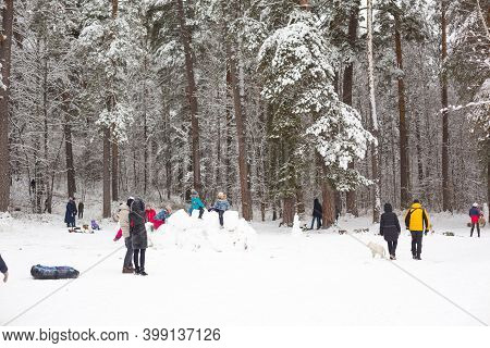 People Walk In Snowy Winter Forest With Their Families, With Skis, Sleds, Inflatable Tubing, Roll Do