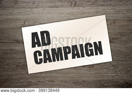 The Words Ad Campaign On The Card On Wooden Table. Advertising Marketing Concept