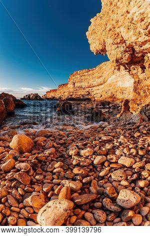 Large Sea Pebbles On The Shore, Large Rocks, Rocks And The Sea In The Sunset. Blurred Front Focus, N
