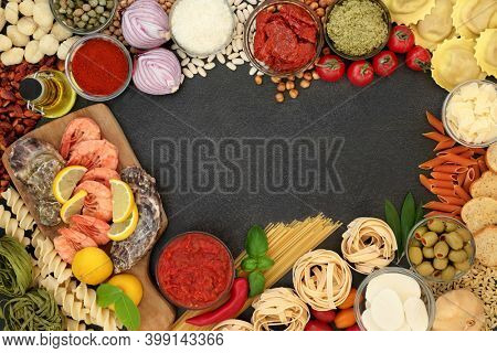 Mediterranean food for a healthy diet border with seafood, pasta, sauces, vegetables, herbs, legumes, olive oil and cheeses. Low in cholesterol, high in antioxidants, fibre and anthocyanins