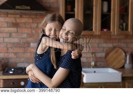Close Up Happy Sick Hairless Mother And Little Daughter Cuddling