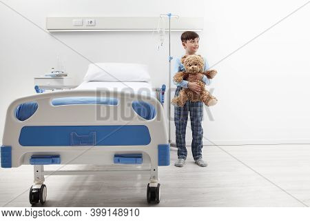 Happy Child In Hospital Room Standing Next To Bed With A Teddy Bear Wearing A Pajama Isolated On Whi