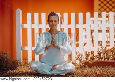 Beautiful Peaceful Female Doing Yoga Exercises in Morning Backyard. Meditating with Closed Eyes in Lotus Posture. Healthy Lifestyle. Body Mind and Soul. Mental Health. Mindfulness Concept. Namaste.