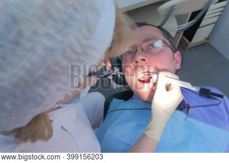 Dentist Examining Gums Of Patient With Probe And Needle Using Method Of Computer Diagnostics. Measur