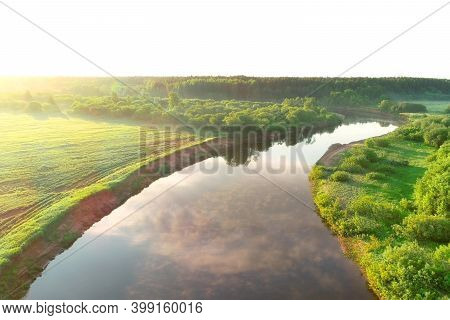 Flying Over River And Green Forest At Summer Sunny Day, Sky Reflecting In Water. Sunrise On Nature I