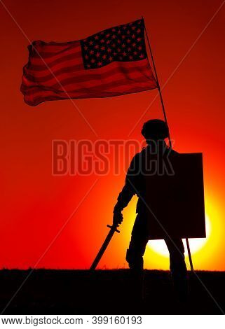 Silhouette Of American Army Soldier Armed Sword And Shield Standing Under Waving Us National Flag On