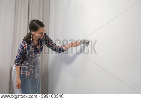 Woman House Painter Is Painting Wall In Grey Using Brush Doing Renovation At Home, Side View. Diy Pr