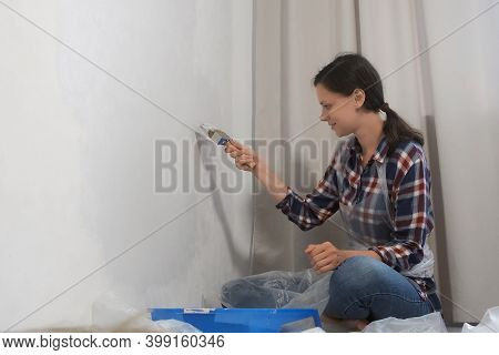 Woman House Painter Is Painting Wall In Grey Using Brush Doing Renovation At Home Sitting On Floor.