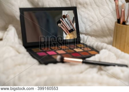 A Collection Of Professional Makeup Brushes And An Eyeshadow Palette. Brushes Are Reflected In The M