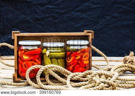 Wooden Crate With Glass Jars With Pickled Red Bell Peppers And Pickled Cucumbers (pickles) Isolated.