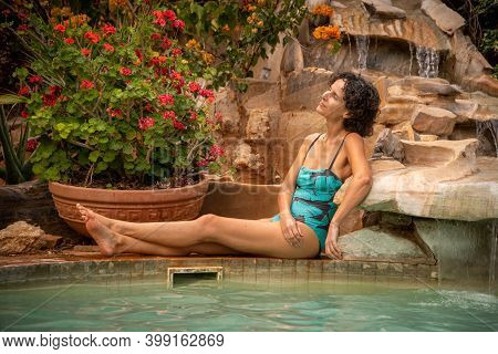 Brunette Sits By Water Feature Cocking Head