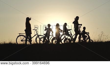 Silhouettes Of A Large Large Family Waving Their Hands To The Sun With Bicycles And Dogs At Sunset.