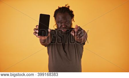 Angry African American Black Man Showing Phone Screen And Pointing Finger Towards Camera. Cheated Hu