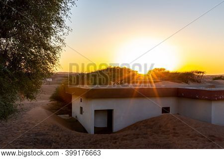 Al Madam Ghost Town Landscape, Residential Buildings Buried In Sand Dunes, Illuminated By Sunset.
