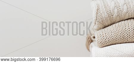 Close Up Stack Of Neatly Folded Warm Knitted Woolen Sweaters On A Beige Background. Capsule Wardrobe