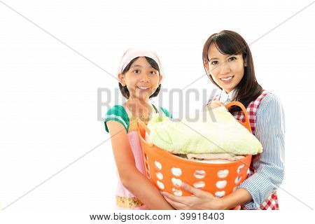 Smiling girl with mother holding a Laundry basket