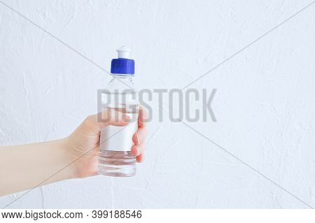 A Transparent Bottle With Colorless Glue In The Hand Of A Caucasian Woman. White Background.