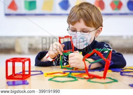 Little Child With Medical Mask Playing With Lots Of Colorful Plastic Blocks Kit In Preschool Nursery