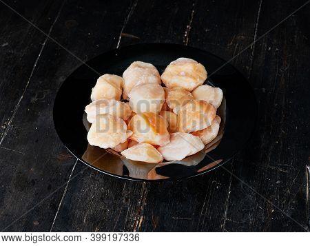 Scallops In A Black Plate. Studio Closeup Of Scallops. Top View.