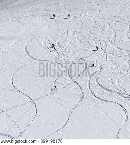 Snowboarders And Skiers Descend On Snowy Off-piste Slope At High Winter Mountains. View From Above.