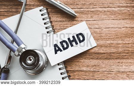 A Card With Text Adhd - Attention Deficit Hyperactivity Syndrome - On Wooden Doctors Table.