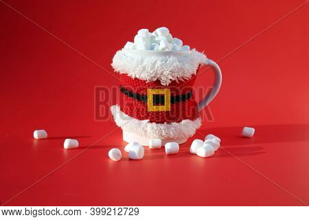 Hot Chocolate with Marshmallows. Santa Claus Cup with Hot Coco and Marshmallows on a Red Background. Christmas time is a good time for Hot Chocolate. Merry Christmas to all.