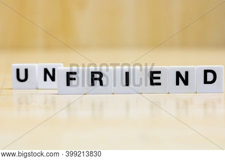 A Row Of Small White Plastic Tiles, Containing The Letters Forming The Word Friend, Unfriend, To Rep