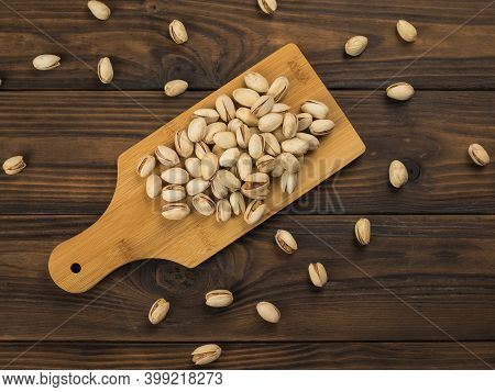 Pistachios On A Cutting Board On A Wooden Table. A Natural Source Of Protein And Carbohydrates.