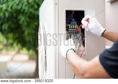 Close Up Hand Of Technician Using Measuring Equipment To Checking Electric Current Voltage At Circui