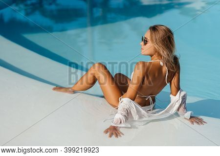 Portrait Of Beautiful Tanned Sporty Slim Woman Relaxing In Swimming Pool Spa. Creative White Shirt A